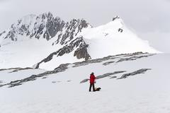 One person standing on the ice in front of a snow-covered mountain. Stock Photos