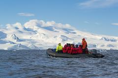Group of people crossing the ocean in the Antarctic - stock photo