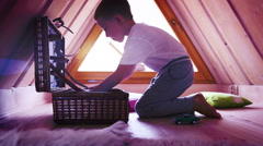 Stock Video Footage of A little boy withdrawing toys from a chest in his attic room