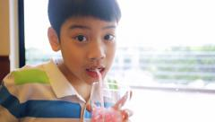 Boy drinking red water after lunch Stock Footage