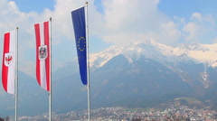 Flags with EU, Austria, Tyrol emblems waving in air, mountains Stock Footage