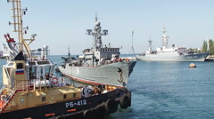 Warship with the help of tugboats moored to the dock Stock Footage