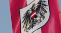 Austrian flag with coat of arms, national emblem waving in sky HD Footage
