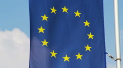 Flag of European Union waving in wind, blue sky background Stock Footage