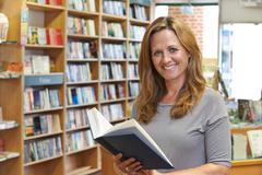 Portrait Of Female Customer Reading Book In Bookstore Stock Photos
