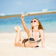 Sexy happy blond young female in sunglasses taking selfie on the beach enjoying - stock photo