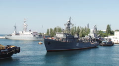 warship with the help of tugboats moored to the dock - stock footage