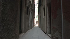 Cameraman with equipment walks in very narrow street of Venice - stock footage