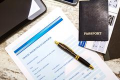 Filling Travel insurance claim form. - stock photo
