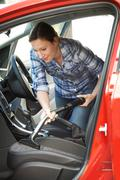 Woman Cleaning Inside Of Car Using Vacuum Cleaner - stock photo