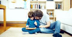 Happy man and son having fun playing with ipad at home Stock Footage