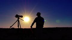Silhouette of  man  photographer  meditate  near camera with sun. 4K 3840x2160 - stock footage