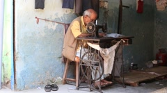 Street tailor working on a foot sewing machine , India Stock Footage