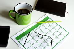 Organizing appointments in the calendar meanwhile drinking a cup of coffee - stock photo