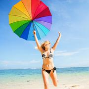 Young skinny girl in blue shorts with colourful rainbow umbrella jumps on the - stock photo