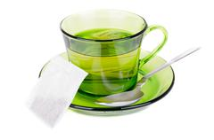 green tea in transparent cup isolated on white - stock photo