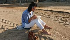 Dark curly hair female reading a book on the beach. Stock Footage