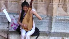 Chinese Street Performer with Pipa (Chinese lute) with music, Lyon, France  Stock Footage