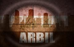 Sniper scope aimed at the abstract silhouette of the city with text Arbil at Stock Illustration