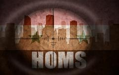 sniper scope aimed at the abstract silhouette of the city with text Homs at t - stock illustration