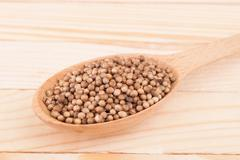 Coriander in a wooden spoon on the table. - stock photo