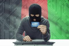 Dark-skinned hacker with credit card and flag on background - Afghanistan Stock Photos