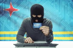Dark-skinned hacker with credit card and flag on background - Aruba - stock photo