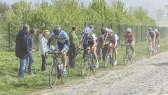 The Peloton on a Cobblestoned Road - Paris - Roubaix 2014 Stock Photos