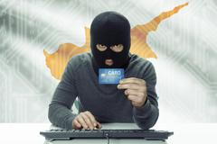 Dark-skinned hacker with credit card and flag on background - Cyprus - stock photo