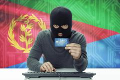 Dark-skinned hacker with credit card and flag on background - Eritrea Stock Photos