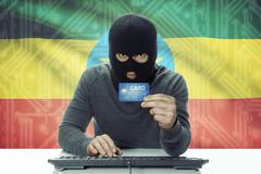 Dark-skinned hacker with credit card and flag on background - Ethiopia Stock Photos