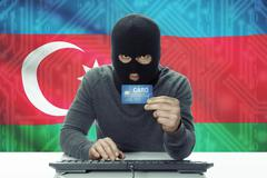 Dark-skinned hacker with credit card and flag on background - Azerbaijan - stock photo