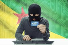 Dark-skinned hacker with credit card and flag on background - French Guiana - stock photo