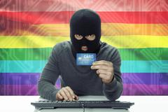 Dark-skinned hacker with credit card and flag on background - LGBT people - stock photo