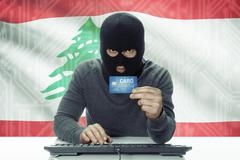 Stock Photo of Dark-skinned hacker with credit card and flag on background - Lebanon