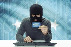 Dark-skinned hacker with credit card and flag on background - Micronesia - stock photo