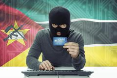 Dark-skinned hacker with credit card and flag on background - Mozambique - stock photo