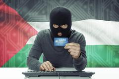 Dark-skinned hacker with credit card and flag on background - Palestine Stock Photos