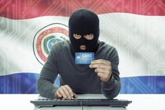 Stock Photo of Dark-skinned hacker with credit card and flag on background - Paraguay