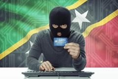 Dark-skinned hacker with credit card and flag on background - Saint Kitts and Stock Photos