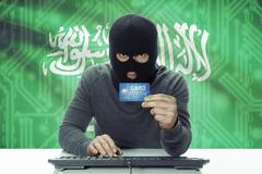 Dark-skinned hacker with credit card and flag on background - Saudi Arabia Stock Photos