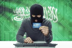 Dark-skinned hacker with credit card and flag on background - Saudi Arabia - stock photo