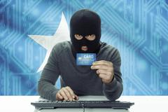 Dark-skinned hacker with credit card and flag on background - Somalia - stock photo