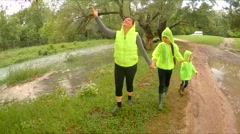 Mother And Two Children Walking In Park After Rain Stock Footage