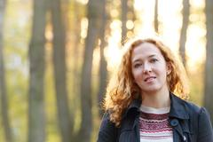 Curly beautiful woman smiles in autumn park at sunny evening Stock Photos