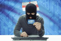 Stock Photo of Dark-skinned hacker with credit card and Canadian province flag on background