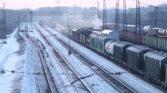 Railways with freight trains on station at winter day. Varifocal lens Stock Footage