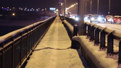 Lot of cars moves on bridge at winter night during snowfall Stock Footage
