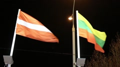 Flags of Austria and Lithuania with illumination on wind at dark night Stock Footage