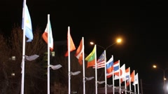 Many flags of different countries on wind at winter night in city - stock footage